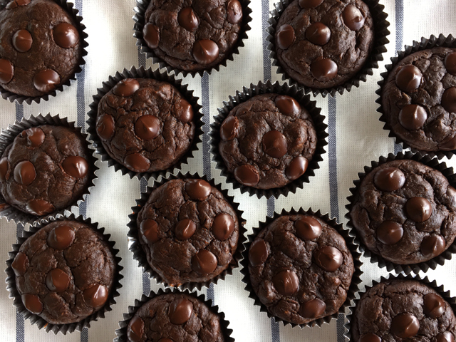 Several Flourless Chocolate Zucchini Muffins on a blue and white striped cloth