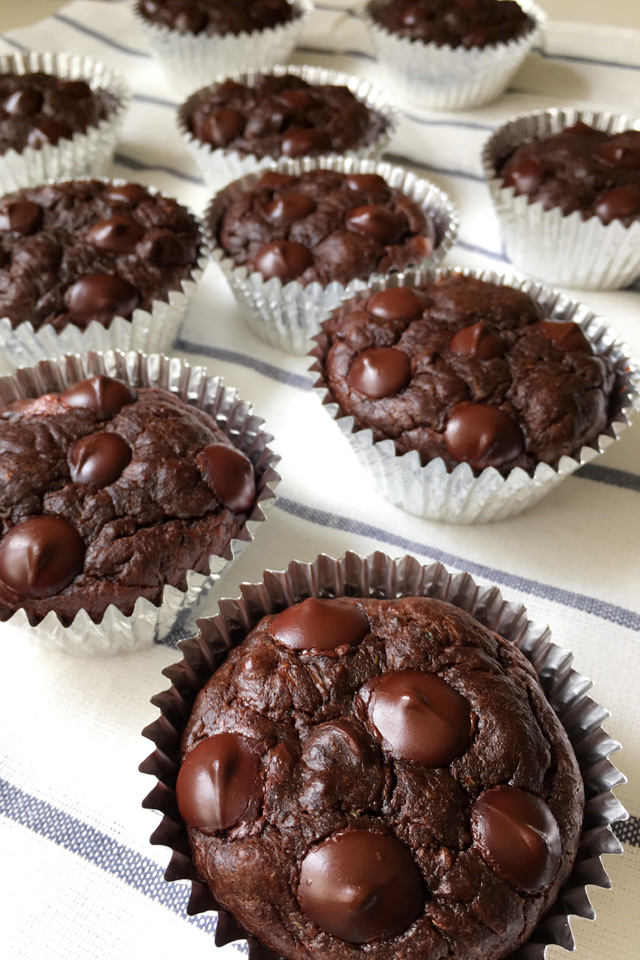 Foil lined Flourless-Chocolate-Zucchini-Muffins on a white and blue striped cloth