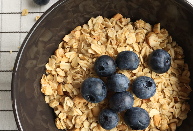 A bowl of granola with blueberries and nuts and blueberries on the table