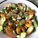 A plate of turmeric shrimp spinach salad