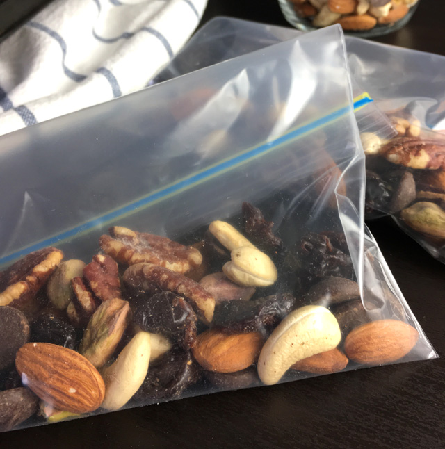 DIY Salty & Sweet Trail Mix made up of cashews, almonds, pistachios, chocolate chips, pecans, and dried cherries in zip top bags