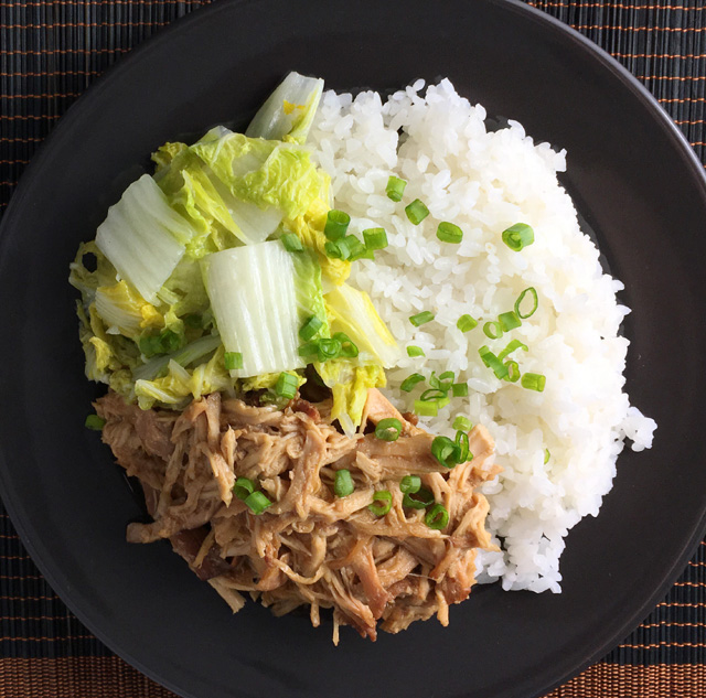 A black plate of Slow Cooker Teriyaki Pulled Chicken with white rice, napa cabbage and chopped green onion