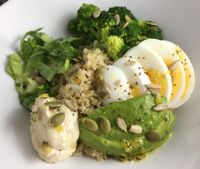 Super Food Quinoa Bowl containing quinoa, hummus, lettuce, broccoli, hard boiled egg, avocado, and sunflower and pumpkin seeds