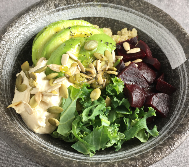 Super Food Quinoa Bowl containing quinoa, avocado, hummus, kale, beets, and sunflower and pumpkin seeds
