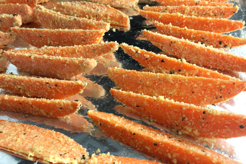 Sweet potato wedges coated in parmesan on a baking sheet for Crispy Sweet Potato Fries