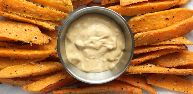 A platter of Crispy Sweet Potato Fries with a dish of chipotle mayo