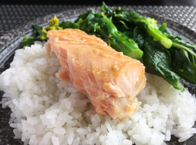 Close-up of a chunk of broiled miso salmon filet on a plate with white rice and leafy green vegetables