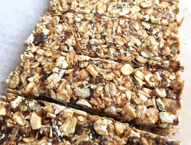 Close-up of cut Simple Nutty Granola Bars containing rolled oats, nuts, and chocolate chips