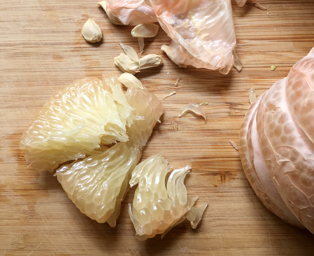 Pomelo wedges on a wooden cutting board for Prawn Pomelo Salad