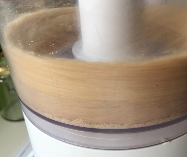 Sesame seeds being processed in a food processor for Easy Homemade Tahini.
