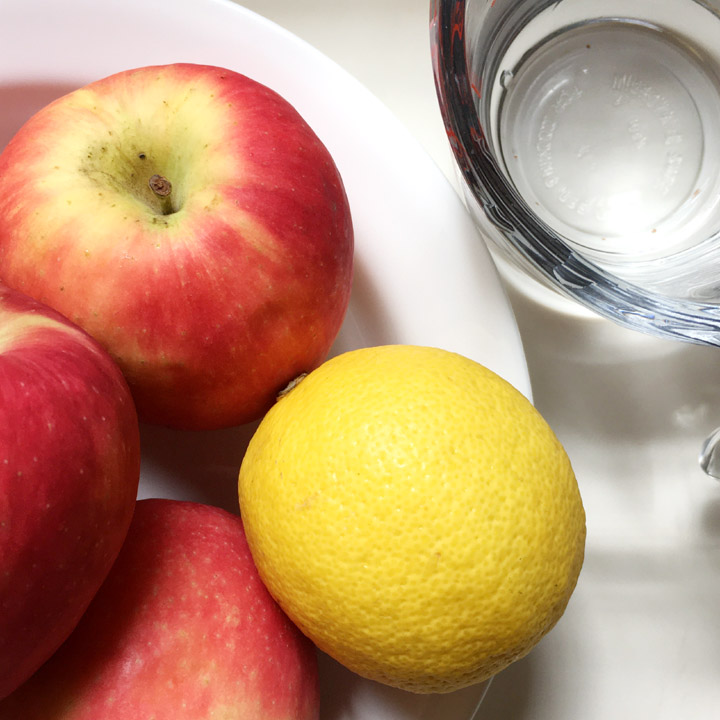 Red apples and a yellow lemon in a white bowl next to a measuring cup containing water