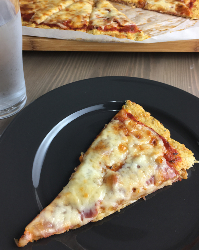 A black plate with a piece of cauliflower crust pizza