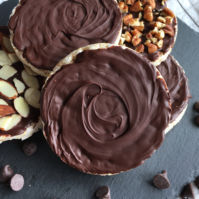 A pile of chocolate coated rice cakes surrounded by chocolate chips on a grey stone platter