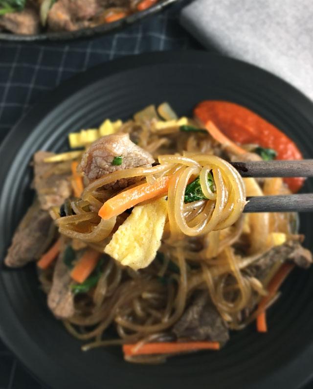 Dark chopsticks holding noodles, beef, egg, carrots over a dish of sweet potato noodles