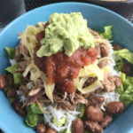 A bowl of pulled pork, rice, beans, cheese, salsa, and guacamole