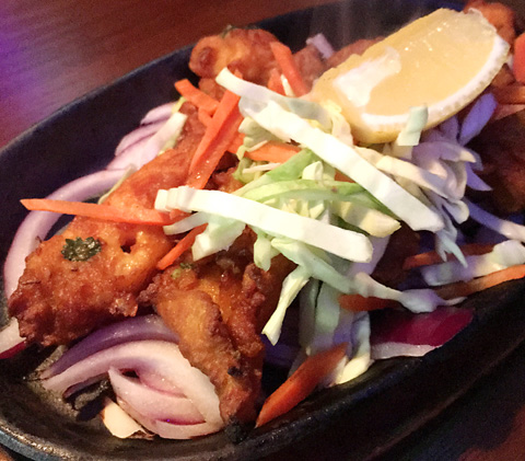 A plate of sizzling Fish Tikka with shredded cabbage and a lemon wedge at Hungry Eye Restaurant