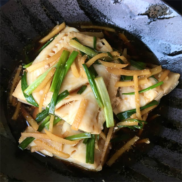 A black dish containing poached black cod with ginger and green onions