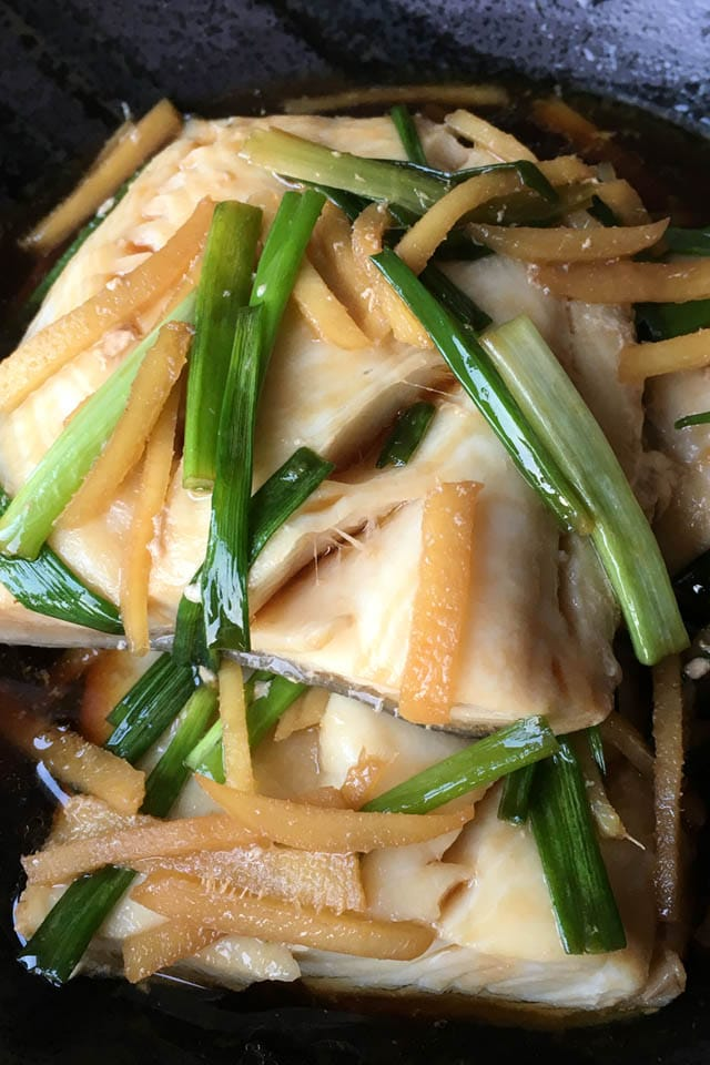 Close-up of poached black cod filets with green onions and ginger