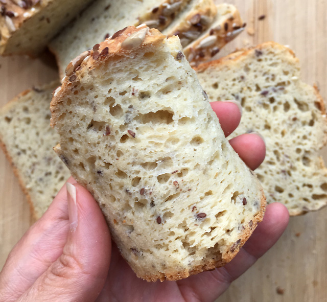 Close-up of a hand curving a slice of gluten-free sandwich bread