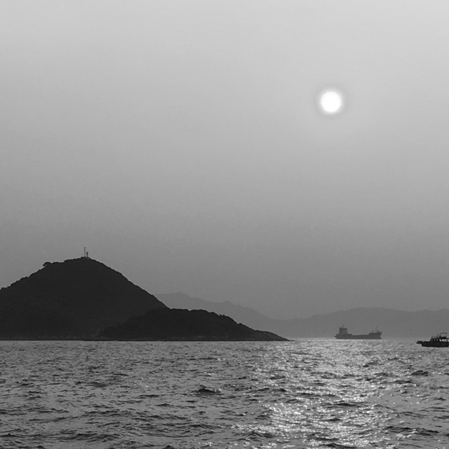 A black and white photo of an island and water and the sun for Hong Kong Friendships