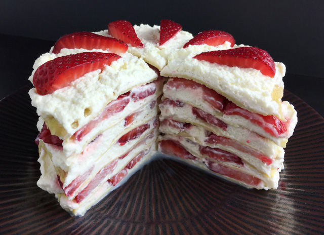 A plate holding Strawberry Cloud Crepe Cake with a piece cut out