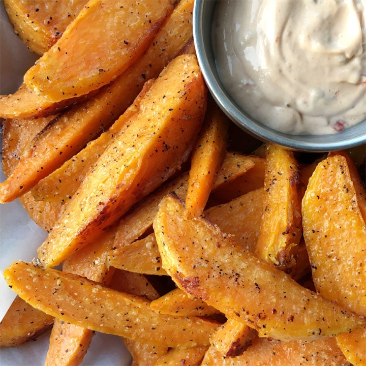 A round silver dish containing a creamy dip, next to sweet potato wedge fries