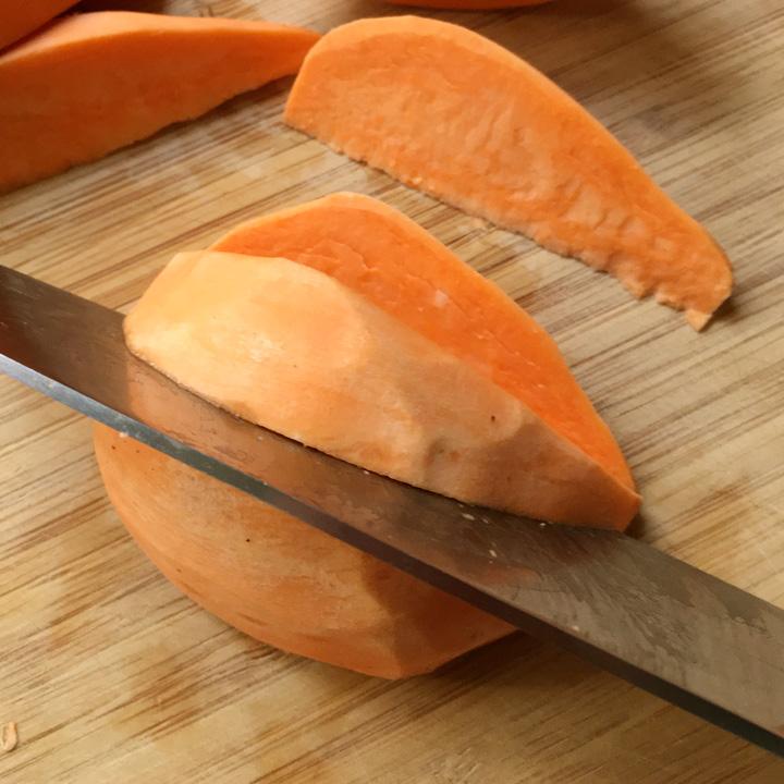 A knife cutting an orange sweet potato into wedges