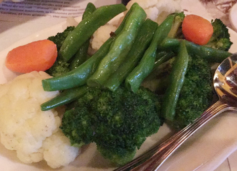 A white plate of cooked cauliflower, broccoli, carrots, and green beans at La Pampa