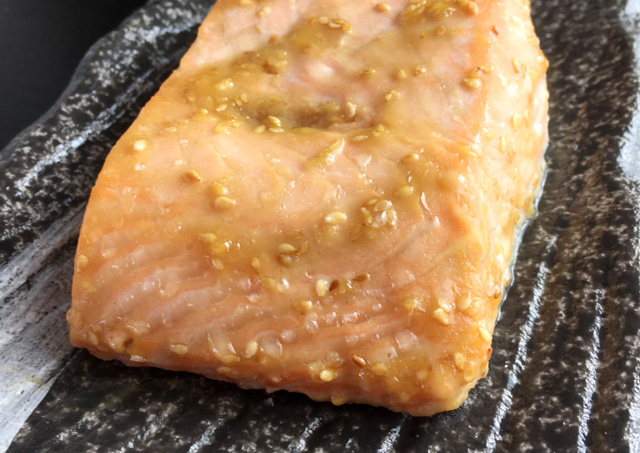 Close-up of one end of a broiled miso salmon filet on a platter