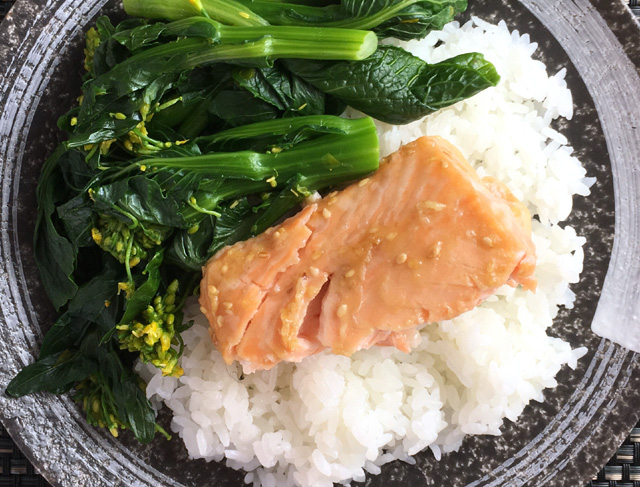 A chunk of broiled miso salmon filet on a plate with rice and leafy green vegetables