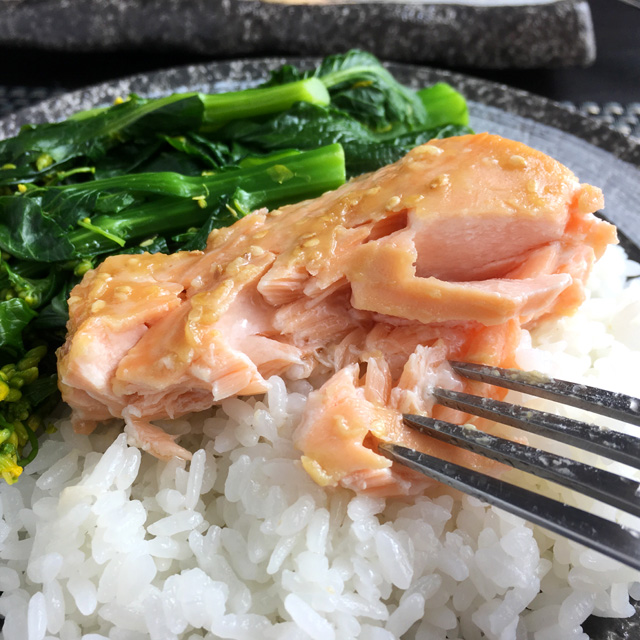 A fork pulling apart some broiled miso salmon filet on a plate of rice and vegetables