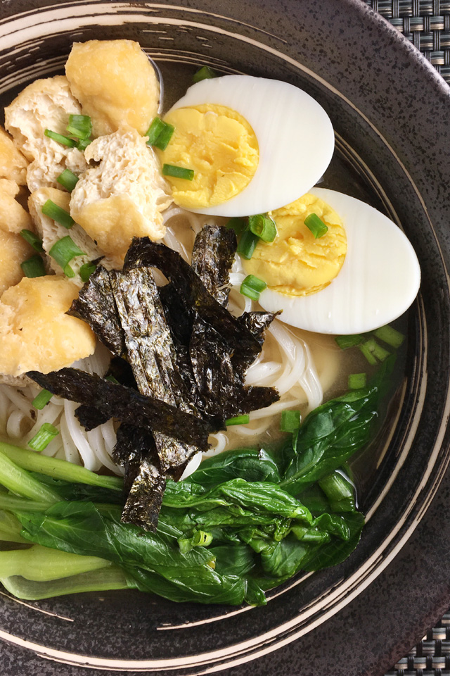 Grey bowl of Miso Noodle Soup containing hard cooked eggs, tofu puffs, leafy Asian greens, white rice noodles, roasted seaweed, and soup.