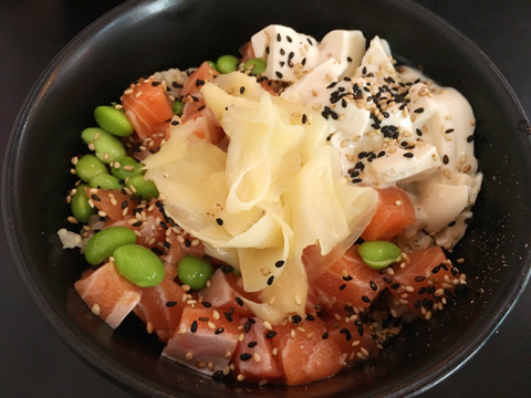 A black bowl containing raw salmon, edamame beans, sliced ginger, tofu, and sesame seeds at Poke HK