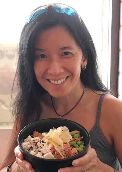 An Asian female holding a black bowl containing tofu, raw salmon, edamame beans, and sliced ginger at Poke HK