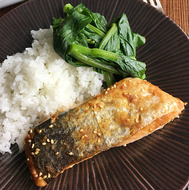 A brown round plate containing a broiled miso salmon filet, white rice, and green vegetables