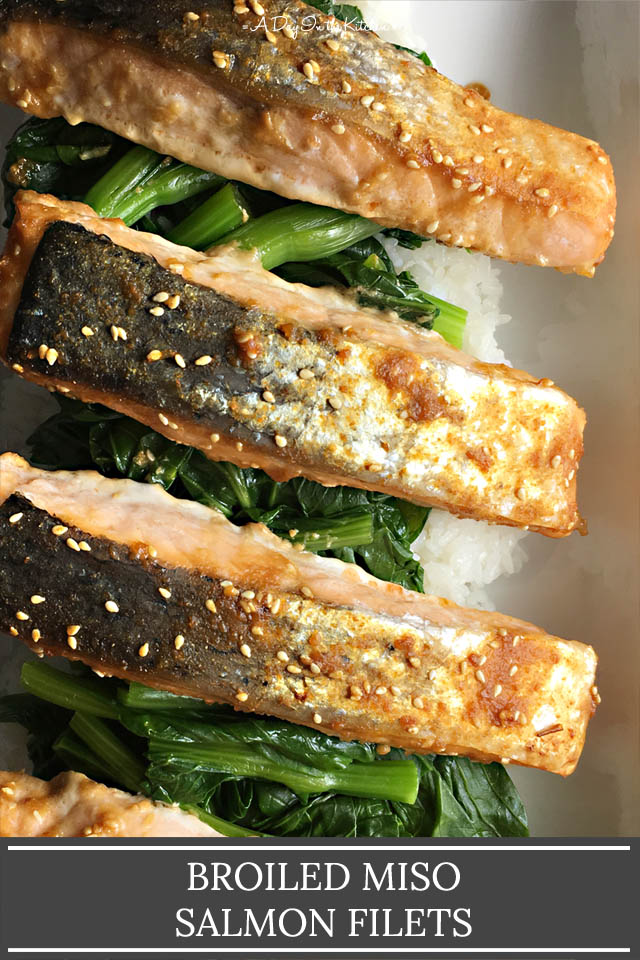 Broiled miso salmon filets on a bed of green vegetables and white rice on a white platter