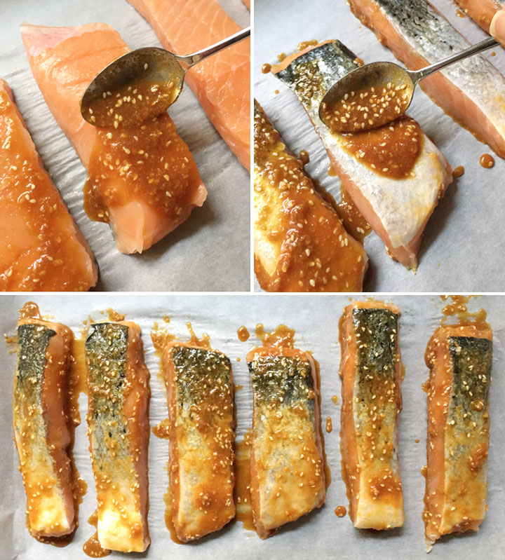 Spreading brown sauce with sesame seeds on salmon filets on a pan