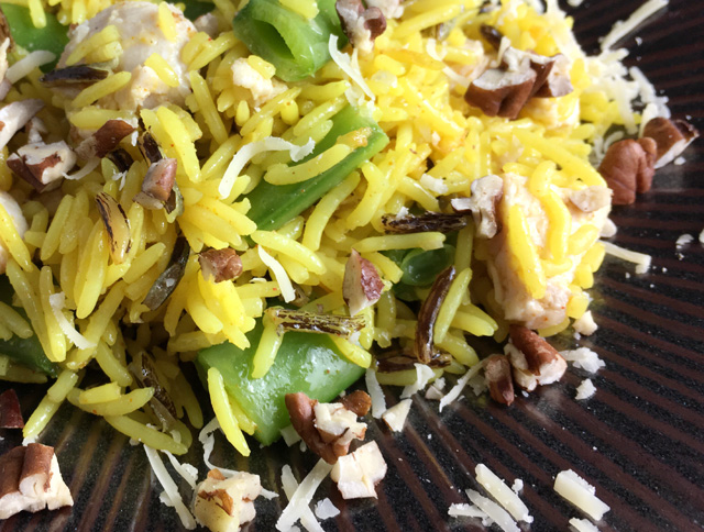 Closeup of a plate of chicken rice salad containing yellow rice, chicken, sugar snap peas, chopped pecans.