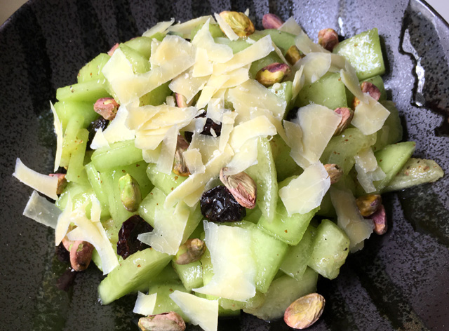 A black bowl of Pistachio Cranberry Melon Salad topped with Parmesan cheese