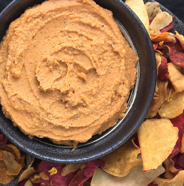A stone bowl containing Roasted Cauliflower Hummus (with tomato paste), surrounded by root chips.