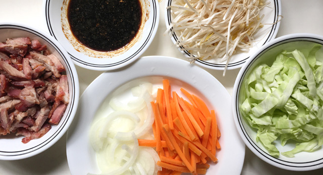 White dishes containing bbq pork, sliced onions, carrots, cabbage, beansprouts, and soy sauce for BBQ pork chow mein