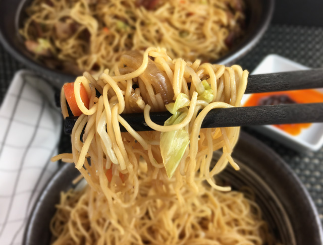 A closeup of a pair of black chopsticks holding BBQ pork chow mein