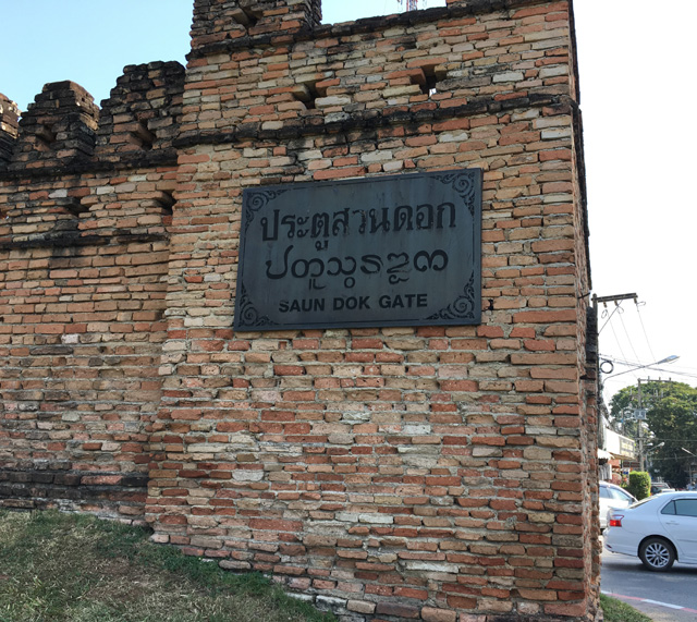 A brick wall with a sign indicating the West Gate of the Walled Old City in Chiang Mai