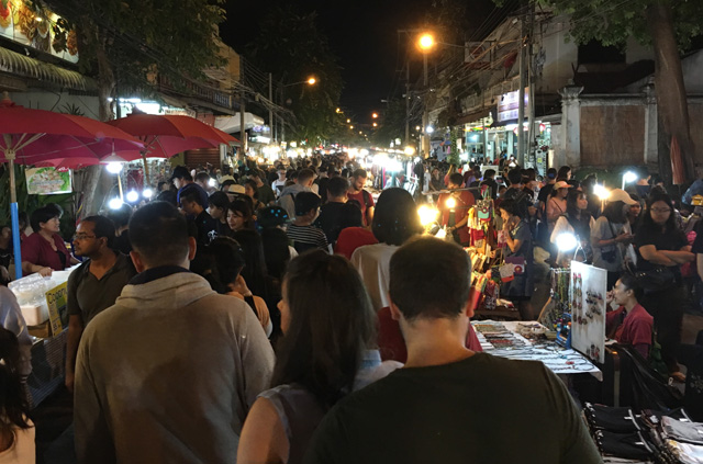 Crowds of people in the street at the Sunday Night Market in Chiang Mai