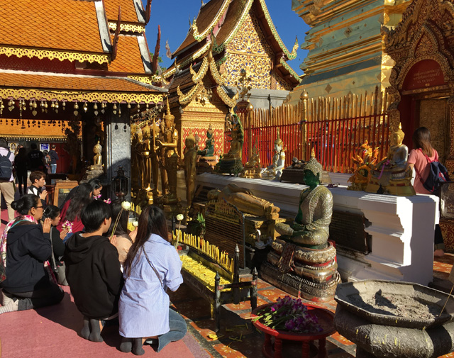 People kneeling and praying at the Golden Temple in Chiang Mai