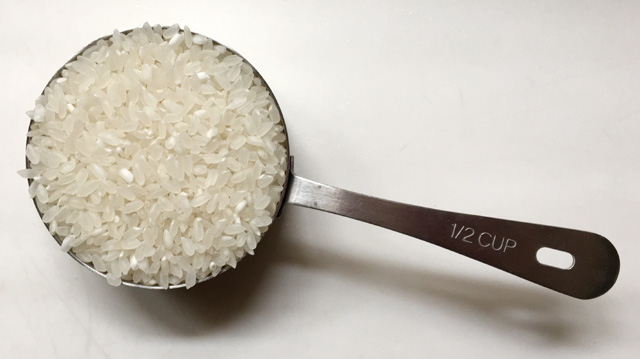 A stainless steel 1/2 cup measuring cup containing rice for Chinese rice porridge congee