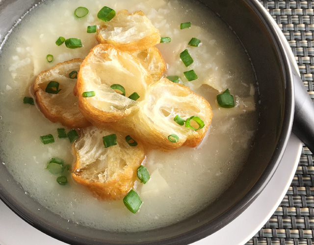 A dark bowl containing Chinese rice porridge congee, chopped green onions, and Chinese doughnut slices