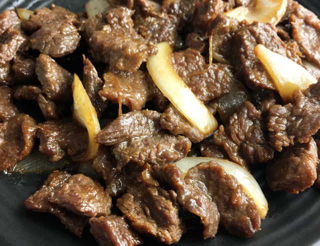 Closeup of cooked steak slices and onions for Korean steak lettuce wraps