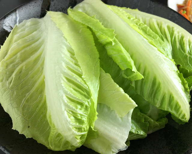 A black plate containing green Romaine lettuce leaves for Korean steak lettuce wraps