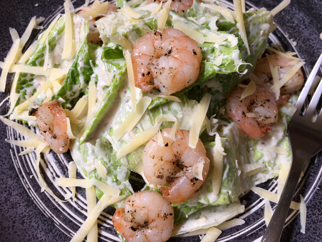 A plate containing green lettuce leaves coated in Greek yogurt Caesar dressing and topped with cooked shrimp and Parmesan cheese